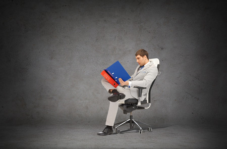 gray suit: business and office concept - handsome businessman in suit with folders sitting on office chair Stock Photo