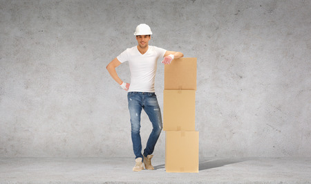 moving office: building, moving and postal concept - smiling man in helmet and gloves with tower of cardboard boxes