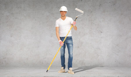 man painting: construction and building concept - handsome painter in helmet with paint roller over concrete wall