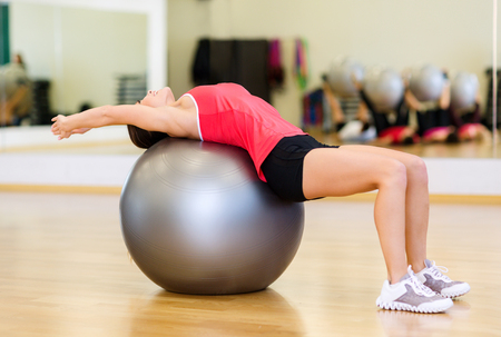 fitness, sport, training, gym and lifestyle concept - young woman doing exercise on fitness ball photo