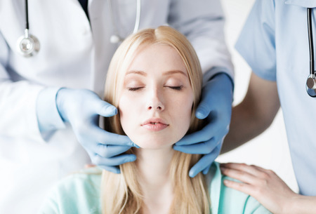 plastic surgery: healthcare, medical and plastic surgery concept - plastic surgeon or doctor with patient Stock Photo