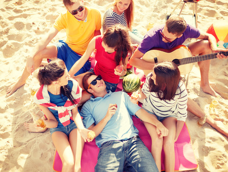 friends party: summer, holidays, vacation, music, happy people concept - group of friends with guitar having fun on the beach
