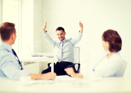 enthusiastic: picture of happy businessman showing thumbs up in office