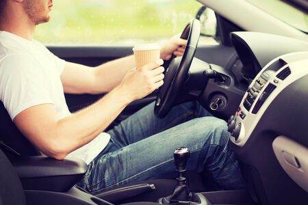 drinking driving: transportation and vehicle concept - man drinking coffee while driving the car