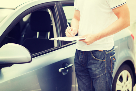 transportation and ownership concept - man with car documents Stock Photo