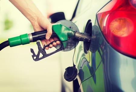 gasolinera: el transporte y la propiedad de concepto - hombre de bombeo de combustible de gasolina en el coche en la estación de gas