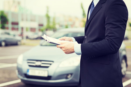car loans: transportation and ownership concept - man with car documents outside
