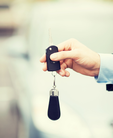 test drive: transportation and ownership concept - man with car key outside