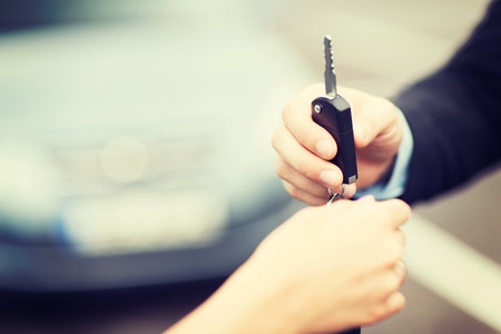 test drive: transportation and ownership concept - customer and salesman with car key outside