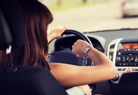 교통 및 차량 개념 - 여자가 차를 운전하고 시계를 찾고