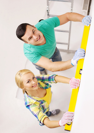 repair, building and home concept - smiling couple building new home using spirit level to measure photo