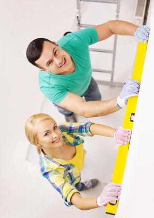 metro de medir: reparación, construcción y concepto de hogar - sonriente pareja nuevo hogar del edificio utilizando el nivel de burbuja para medir