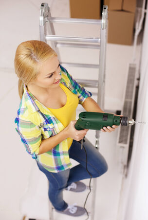 repair, building and home concept - smiling woman with electric drill making hole in wall photo