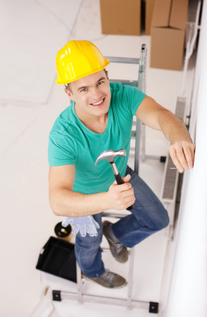 repair, building and home renovation concept - smiling man in yellow protective helmet hammering nail in wall photo