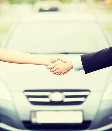transportation, business, shopping and ownership concept - customer and salesman shaking hands outside photo