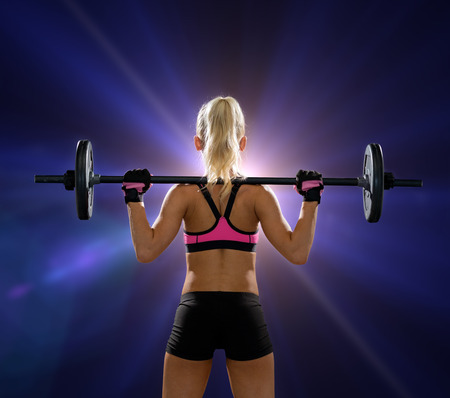 fitness, sport and dieting concept - sporty woman exercising with barbell from back photo