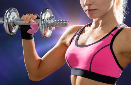 musculine: fitness, healthcare and dieting concept - close up of young sporty woman with heavy steel dumbbell Stock Photo