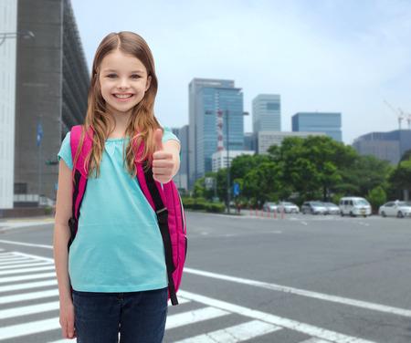 la educación, el gesto y el concepto de la escuela - niña feliz y sonriente con el bolso de escuela que muestra los pulgares para arriba