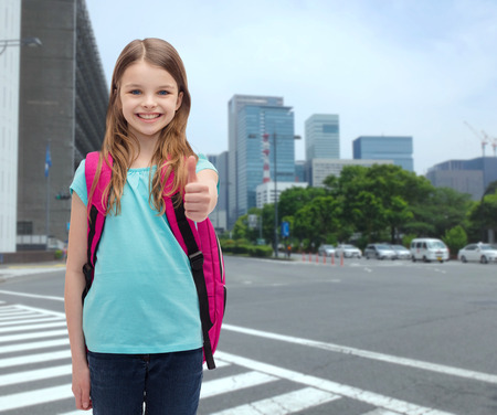 paso de peatones: la educación, el gesto y el concepto de la escuela - niña feliz y sonriente con el bolso de escuela que muestra los pulgares para arriba