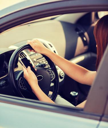 transport en voertuig concept - vrouw met behulp van telefoon tijdens het rijden de auto Stockfoto