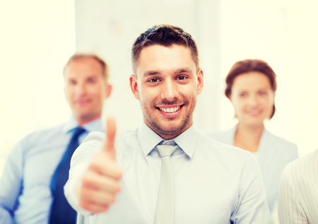 attractive businessman in office showign thumbs up photo