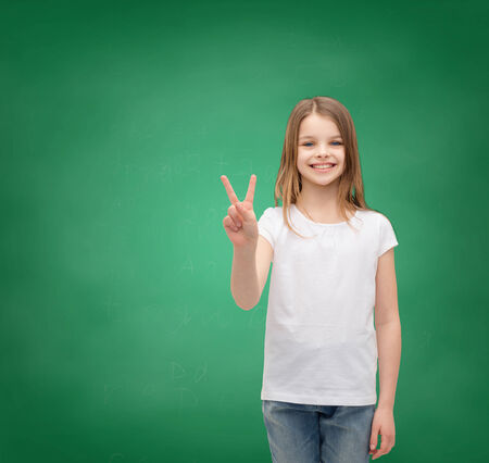 gesture and happy people concept - smiling little girl in white blank t-shirt showing peace gesture with fingers photo