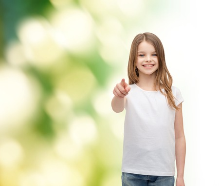 gestures and happy people concept - happy little girl in blank white t-shirt pointing at you photo