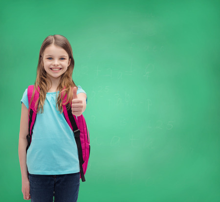 education, gesture and school concept - happy and smiling little girl with school bag showing thumbs up photo