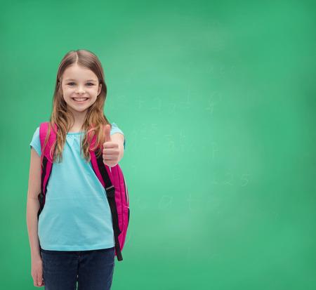 onderwijs, gebaar en schoolconcept - het gelukkige en glimlachende meisje met schooltas die beduimelt omhoog toont