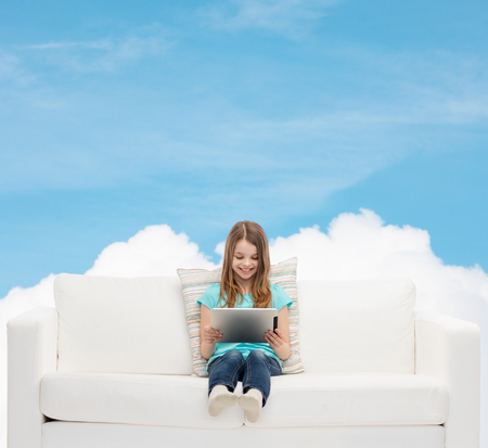 home, leisure, technology and happiness concept - smiling little girl sitting on sofa with tablet pc computer photo