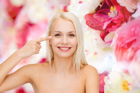 health and beauty concept - face of beautiful woman touching her eye area photo