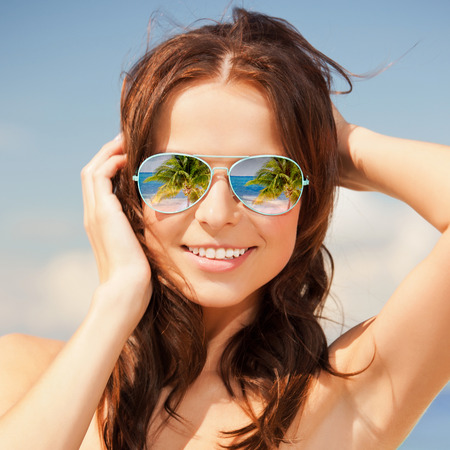 holidays, travel, vacation and happiness concept - beautiful woman in sunglasses with beach reflection photo