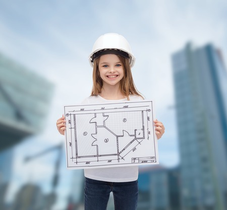 building, developing, construction and architecture concept - smiling little girl in white helmet showing blueprint photo