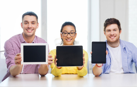 entrepreneurs: education, technology, business, startup and office concept - three smiling colleagues showing tablet pc blank screen Stock Photo