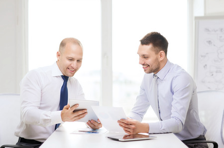 business, technology and office concept - two smiling businessmen with tablet pc computers and files in office photo
