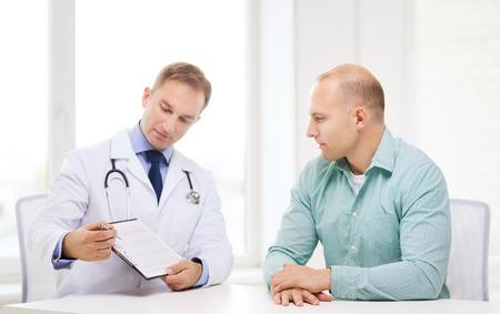 healthcare and medicine concept - serious doctor with clipboard and patient in hospital photo