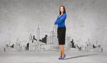 business woman standing: business and office concept - friendly young smiling businesswoman