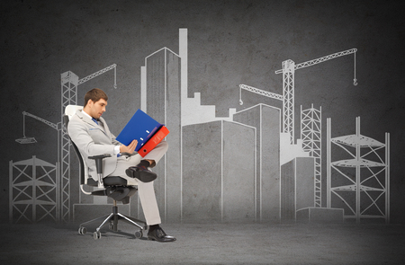 man in chair: business and office concept - handsome businessman in suit with folders sitting on chair Stock Photo