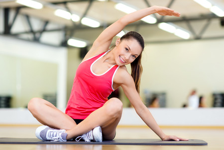 nice body: fitness, sport, training, gym and lifestyle concept - smiling woman stretching on mat in the gym Stock Photo