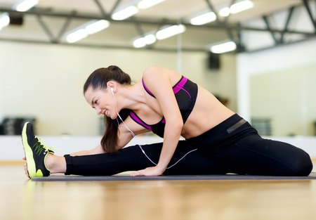 fitness, sport, training, gym and lifestyle concept - smiling woman stretching on mat in the gym photo