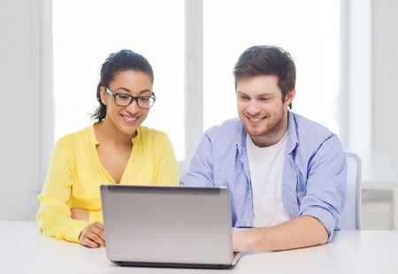 education, technology, business, startup and office concept - two smiling people with laptop in office photo