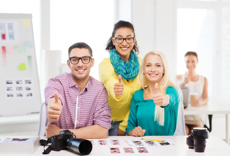 business, education, photography, office and startup concept - smiling creative team with printed photos working in office photo
