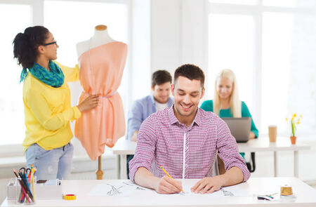 creating: startup, education, fashion and office concept - smiling male drawing sketches and female adjusting dress on mannequin in office