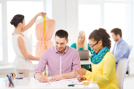 adjusting: startup, education, fashion and office concept - smiling designers drawing sketches and adjusting dress on mannequin in office