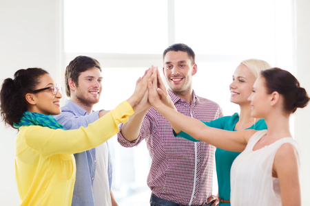 business, office, gesture and startup concept - smiling creative team doing high five gesture in office photo