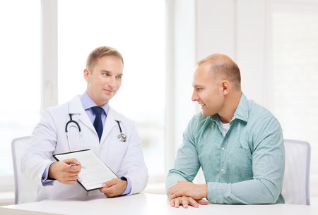 urologist: healthcare and medicine concept - smiling doctor with clipboard and patient in hospital Stock Photo
