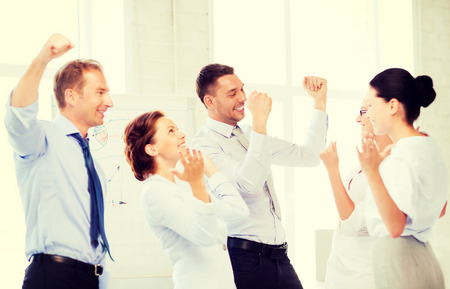 team victory: picture of happy business team celebrating victory in office