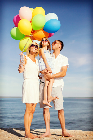 summer holidays, celebration, children and people concept - happy family with colorful balloons at seaside photo