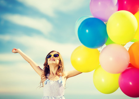 kid's day: summer holidays, celebration, family, children and people concept - happy girl with colorful balloons