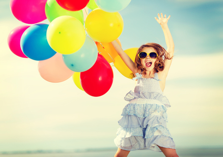 summer holidays, celebration, children and people concept - happy jumping girl with colorful balloons outdoors photo